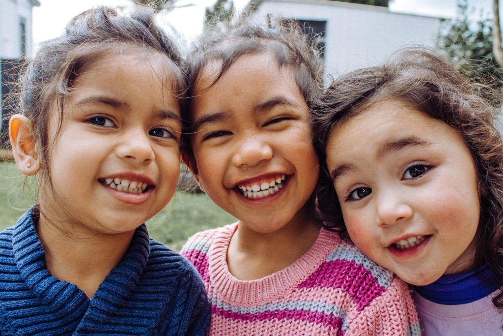 3 small children smiling together
