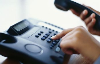 a person dialing a phone